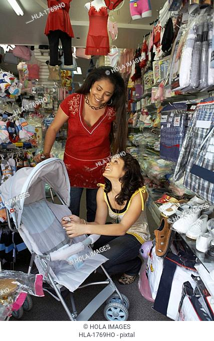 Two young women holding a baby stroller in a baby shop