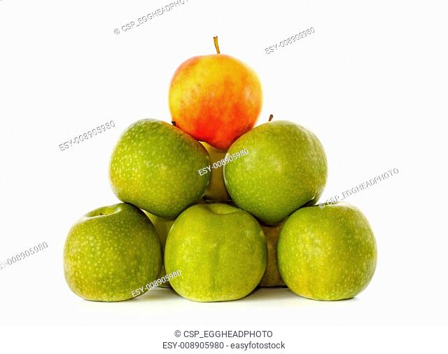 Stack of green apples and one yellow with red blush on top