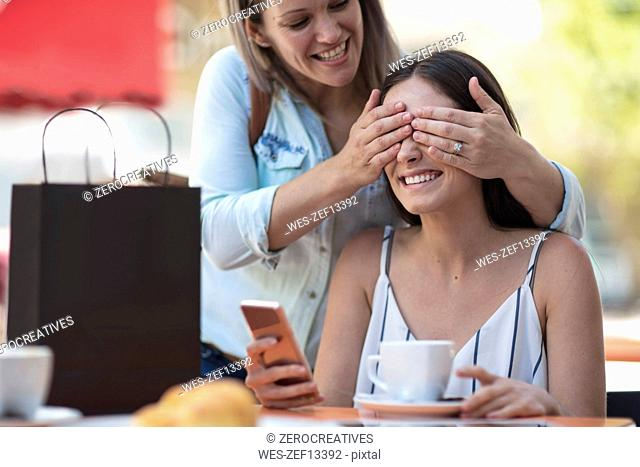 Woman covering eyes of her friend at an outdoor cafe