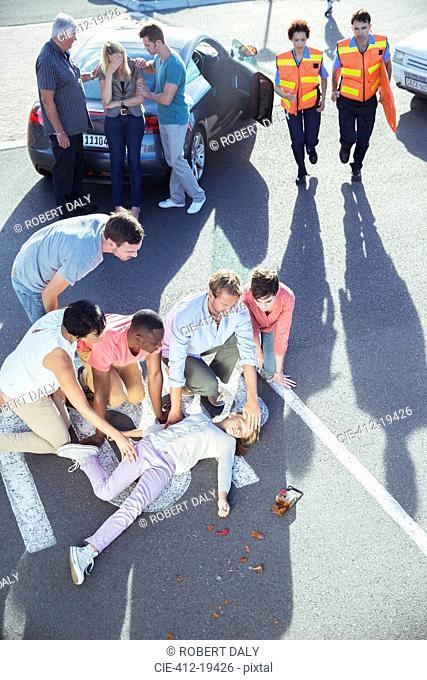 People examining injured girl on street
