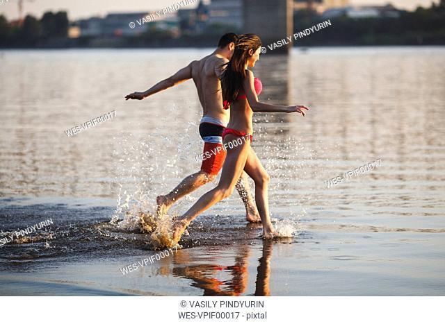 Happy couple running in water
