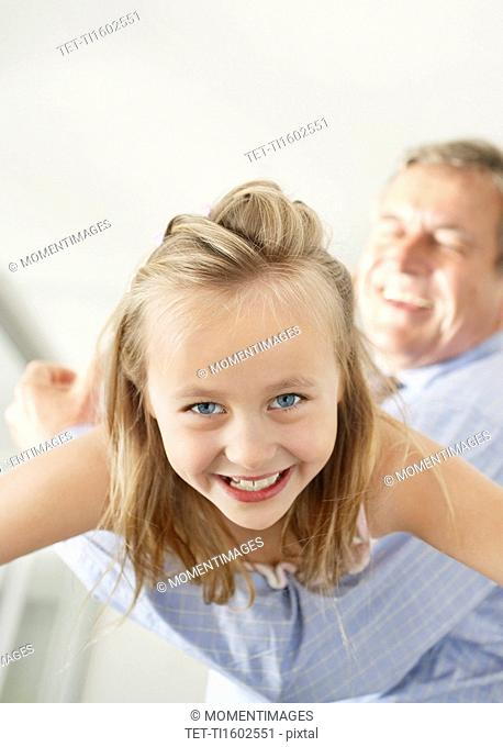 Grandfather playing with granddaughter 10-11