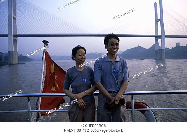 Close-up of a young couple standing on a cruise ship, China