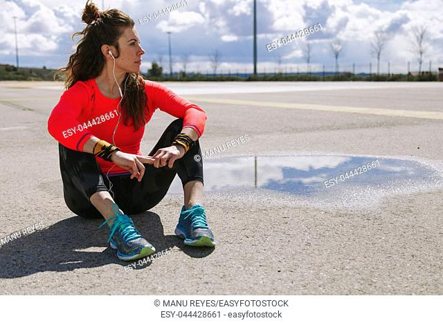 Young woman resting sitting on the floor after run listening music with headphones