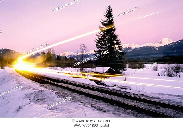 Train light shows speed along winter train tracks, alpenglow behind, Whistler, BC