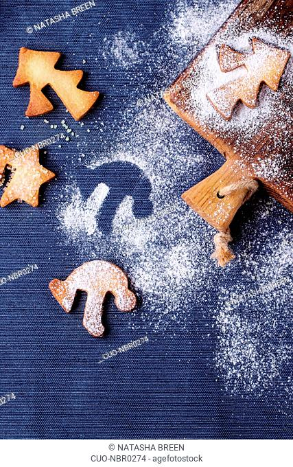 Shortbread Christmas cookies for cups in sugar powder and small cutting board over table with blue tablecloth. Top view. Shape as Christmas tree