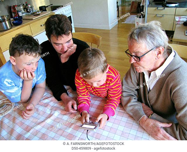 Grandmother, daughter and mother of two sons, 8 and 5, look on as boy plays Gameboy game. Stockholm, Sweden