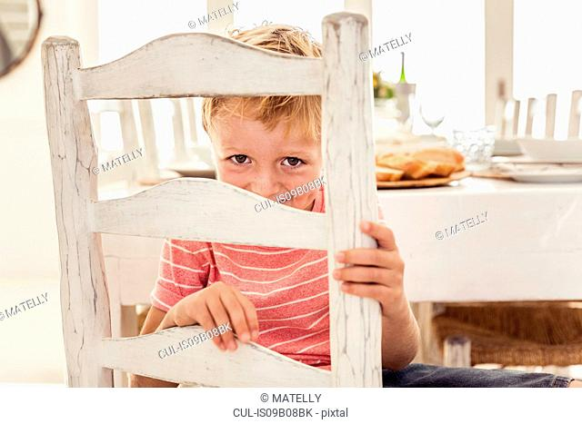 Boy on chair at dining table peeking at camera