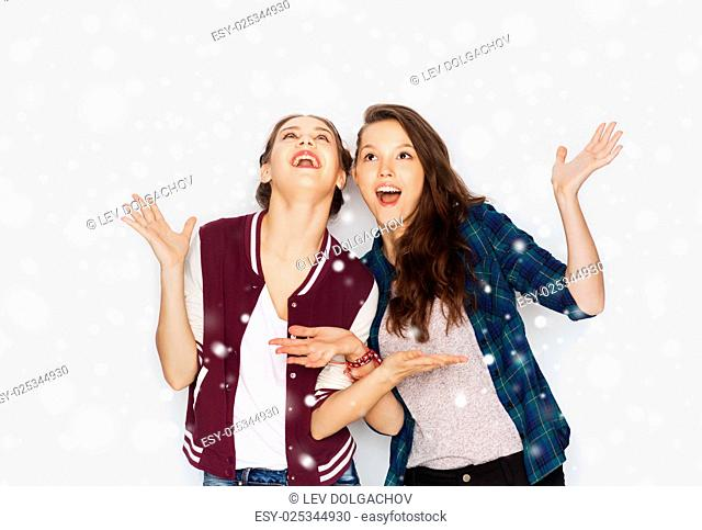 winter, christmas, people and holidays concept - happy smiling pretty teenage girls or friends over gray background and snow