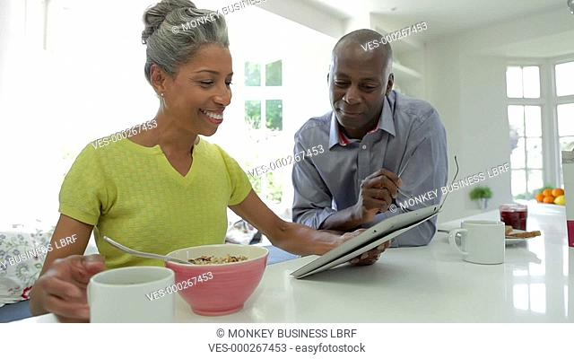 Mature African American couple looking at digital tablet whilst eating breakfast.Shot on Canon 5d Mk2 with a frame rate of 25fps