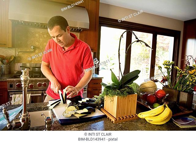 Caucasian man chopping vegetables in kitchen