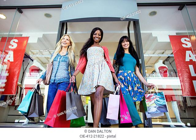 Low angle view of women carrying shopping bags out of clothing store