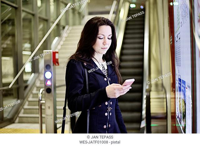 Portrait of young woman looking at cell phone in underground station