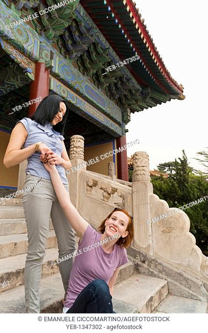 Tourist trying to lift her friend in The Forbidden City, Beijing, China, Asia  MR