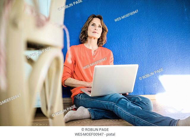 Woman sitting on the floor at home with laptop