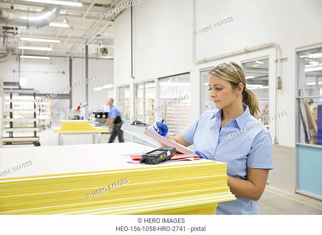 Worker writing on clipboard in factory