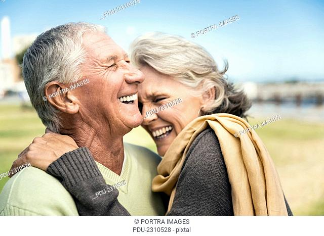 Side view of happy senior couple embracing in park