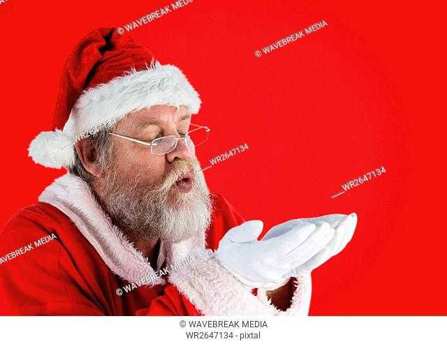 Santa claus pretending to blow imaginary snow