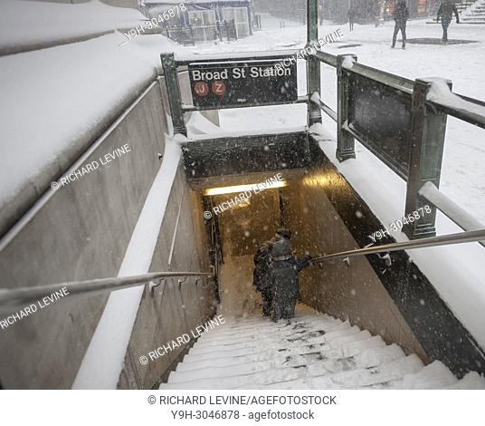 Intrepid travelers maneuver the treacherous snow covered stairs to enter the subway in Lower Manhattan during the first nasty winter storm of the new year on...