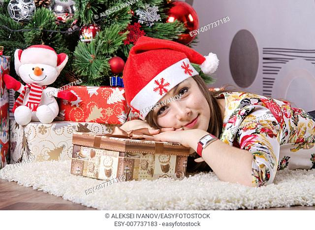 The girl lying on the carpet around the Christmas tree. In her hands a big box with a present. The girl looks frame