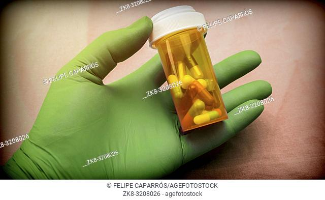 Nurse supports capsules bottle with left hand with glove of green latex in a hospital