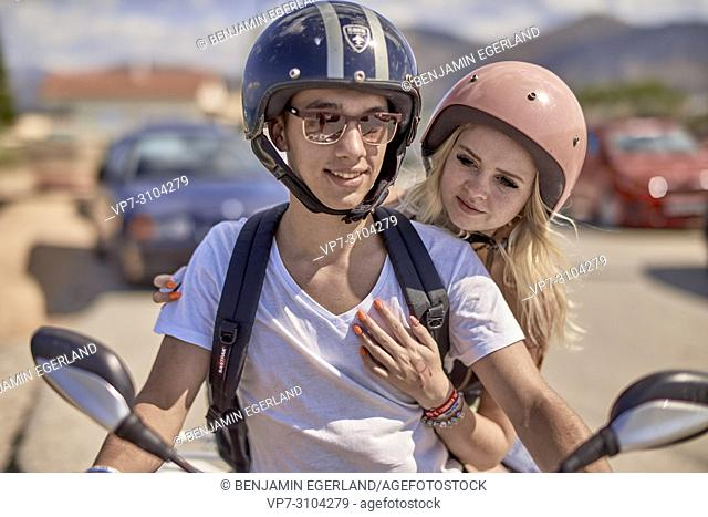 Greece, Crete, Chersonissos, couple driving quad, wearing helmets