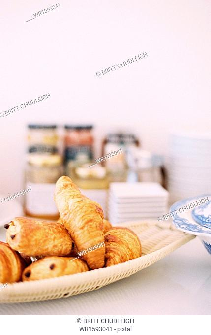 A table with a dish of croissants and pains au chocolat