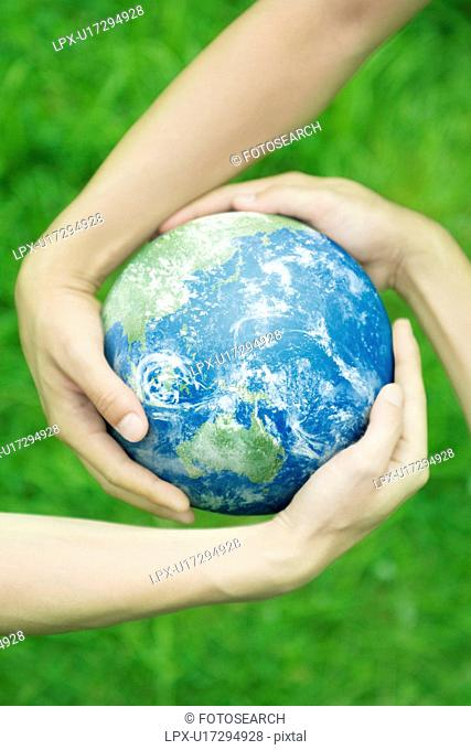 Three People Holding Earth