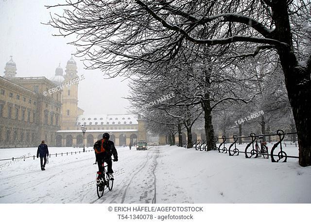 Bicyclist rides in snow by the Hofgarten in Munich