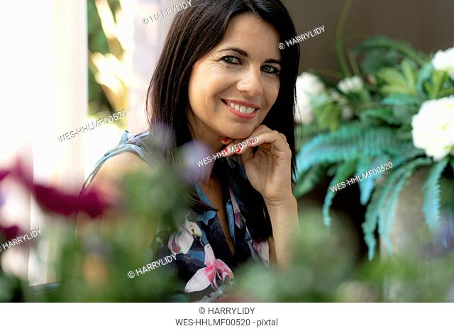 Portrait of smiling dark-haired woman at home