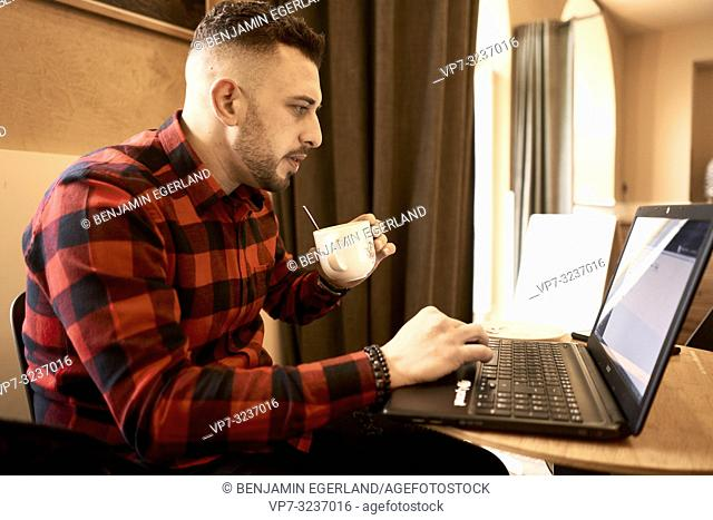 man working with laptop indoors in café, drinking coffee, casual shirt, freelancer, self employee, Greek ethnicity, in Munich, Germany