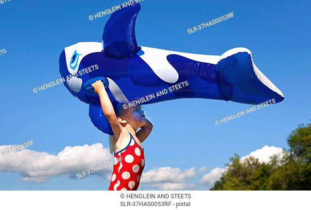 Girl holding inflatable whale outdoors