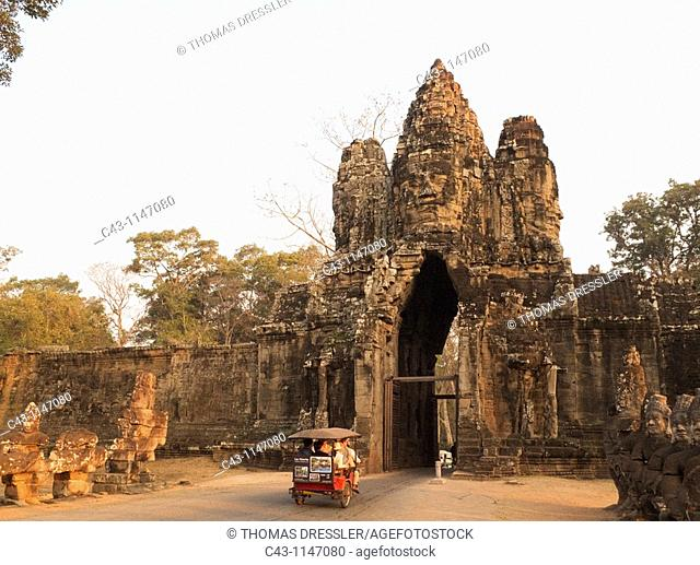 Cambodia - Tuk-tuk at the South Gate of Angkor Thom, the 'Great Capital' of the Khmer empire in Angkor, with the face of Lokeshvara 'Lord of the World'  The...