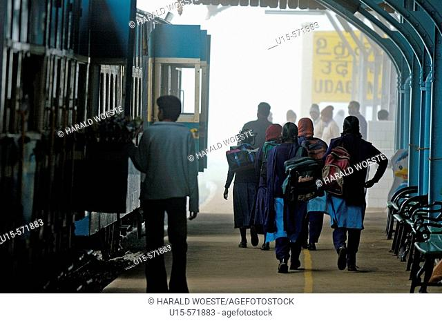 On a foggy day, indian schoolgirls leaving the Nilgiri Mountain Railway and exiting Ooty railway station. Ooty (Udhagamandalam), Tamil Nadu, India 2005