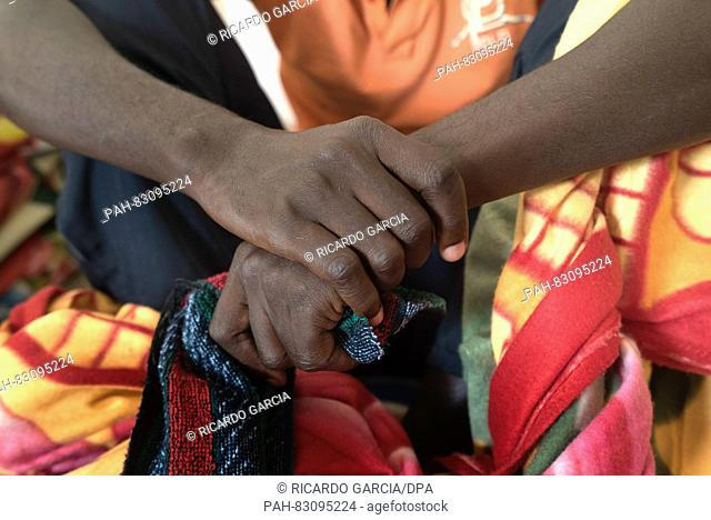 Detail of the hands of an immigrant from Ivory Coast sitting in the Detention Center for ilegal immigrants of Al Karrareiy in Misrata, Lybia, 25 August 2016