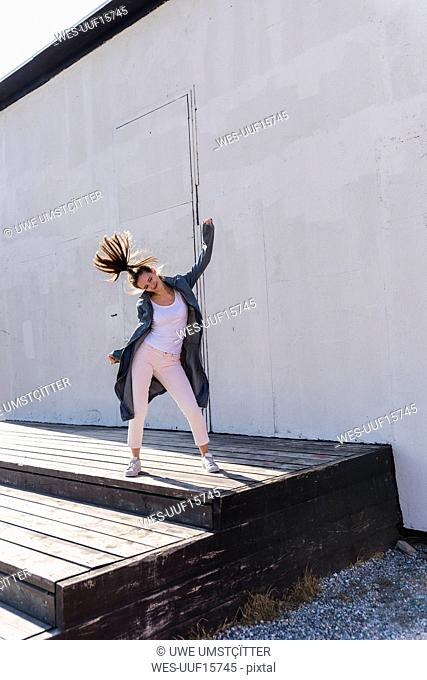 Happy young woman moving in front of a wall
