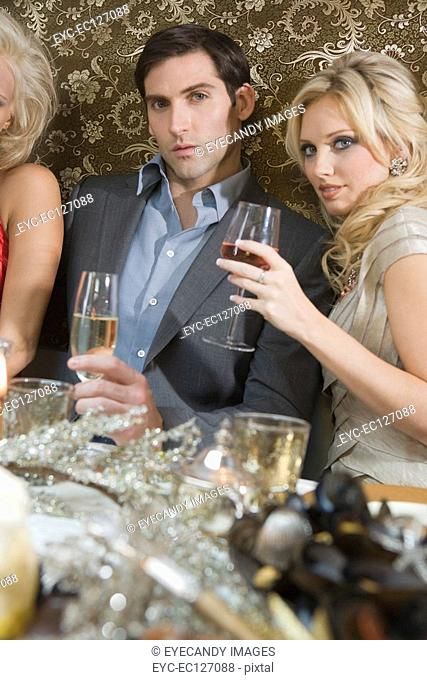 Portrait of young couple at dinner party table drinking wine