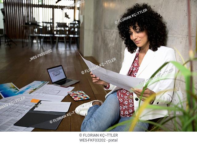 Businesswoman sitting on the floor in a loft working on documents