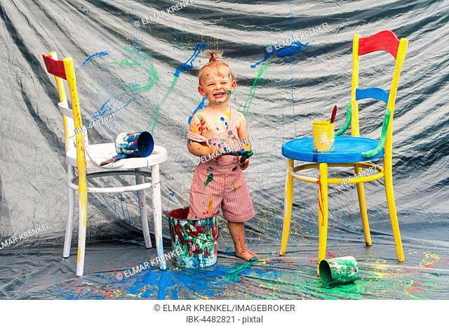 Four year-old girl standing with feet in paint pot, Austria