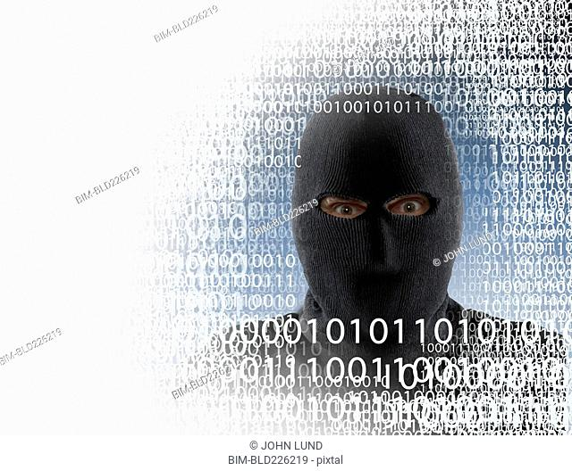 Hacker wearing mask in binary code
