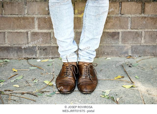 Leather shoes of a man, standing in front of brick wall