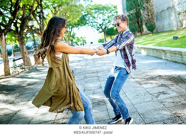 Happy young couple dancing together on pavement