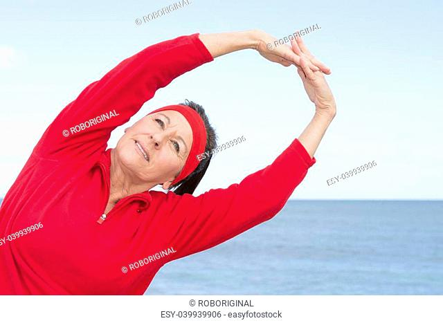 Portrait beautiful middle aged woman showing active retirement, stretch excercising arms up outdoor, positive, confident, smiling