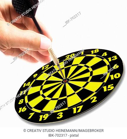 Hand holding dart in action, aiming for the bullseye