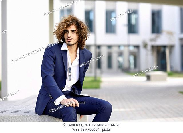 Portrait of young businessman with curly hair wearing blue suit sitting on bench outdoors