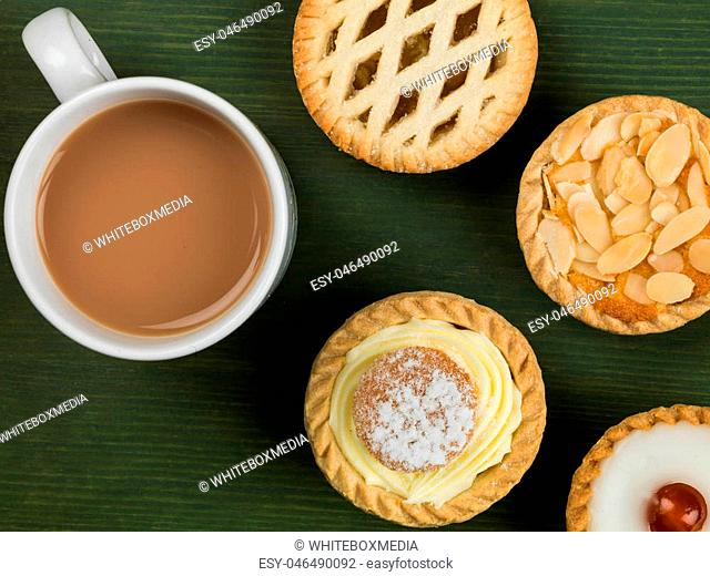 Selection of Individual Cakes or Tarts With a Mug of Tea Against a Green Background