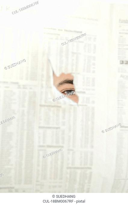 Man spying through hole in newspaper