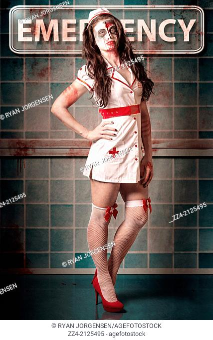 Sexy zombie medical emergency nurse standing in the hospital ER waiting room with the sick and wounded. Recovery ward