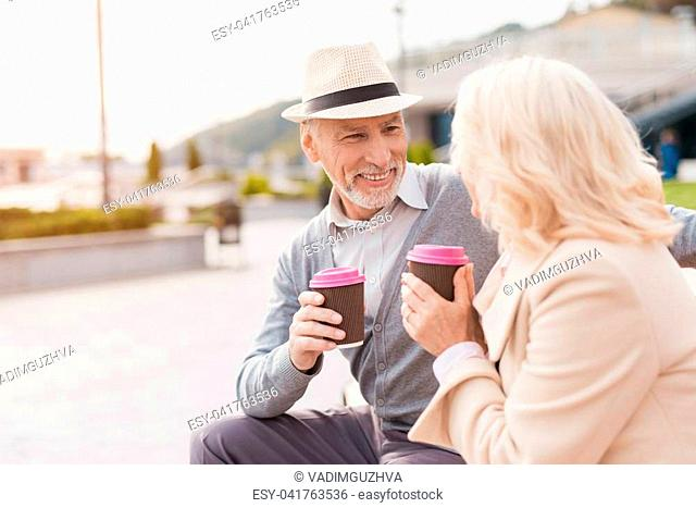 Two pensioners are sitting on a bench with a glass of coffee in their hands. They look at each other with tenderness and smile