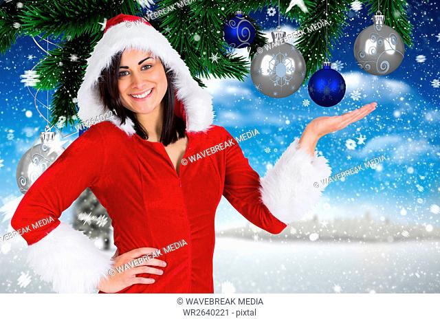 Smiling woman wearing santa costume pretending to hold digitally generated christmas baubles